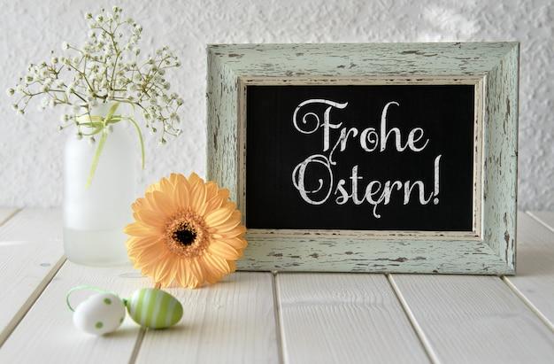 Frühlingsblumen, ostern-dekorationen und eine tafel auf weißer tabelle, text