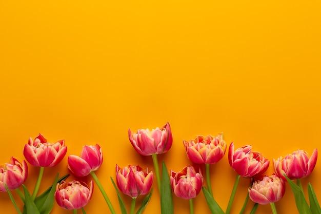 Frühlingsblumen. tulpen auf gelbem hintergrund. grußkarte retro vintage-stil. muttertag, ostergrußkarte.