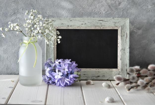 Frühlingsblumen und eine tafel auf weißem tisch, frühlingswand, raum
