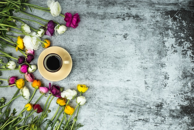 Frühlingsblumen und eine tasse schwarzen kaffee auf grauem marmor hintergrund
