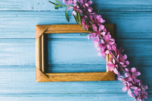Frühlingsblumen und rahmen auf einem blauen hölzernen hintergrund