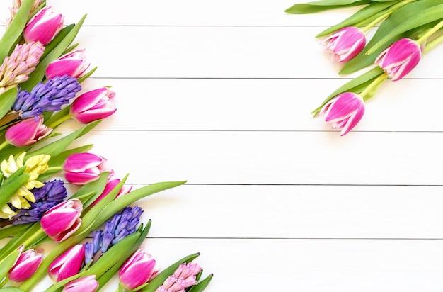 Frühlingsblumengrenze auf weißem holztisch. draufsicht, kopierraum.