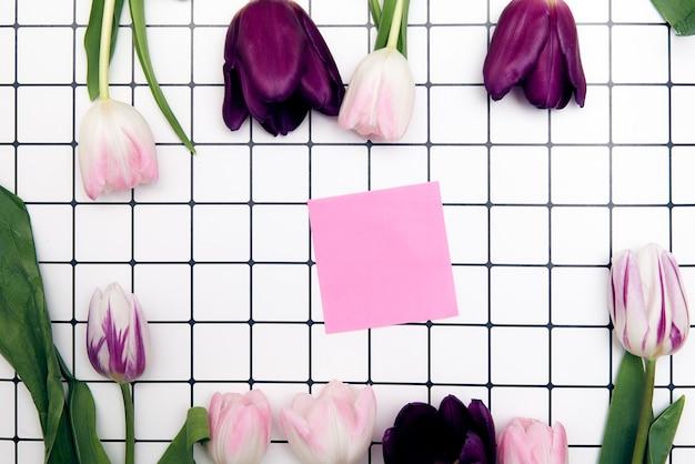 Frühlingsblumenhintergrund mit kopienraum. flacher rahmen aus tulpenblüten mit wassertropfen