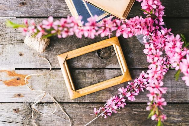 Frühlingsblumenrahmen und buch auf einem alten hölzernen hintergrund
