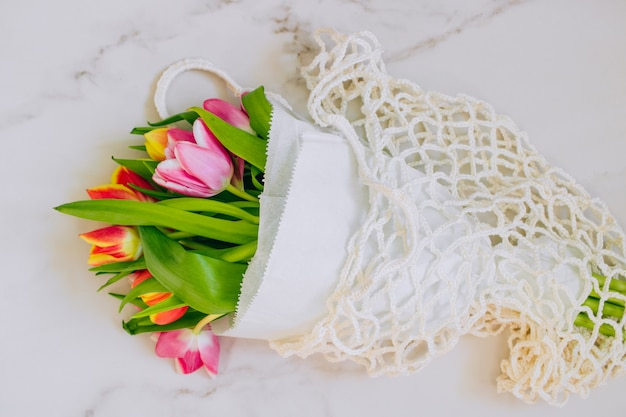Frühlingsblumenstrauß von mehrfarbigen tulpen in der eco tasche auf einem marmorhintergrund. kopieren sie platz, flach legen hintergrund.