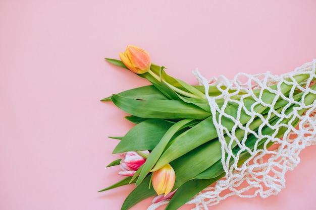 Frühlingsblumenstrauß von mehrfarbigen tulpen in der eco tasche auf einem rosa hintergrund. kopieren sie platz, flach legen hintergrund.