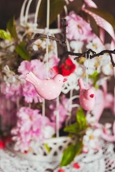 Frühlingsdeko - rosa vögel auf dem ast im shabby chic käfig mit blumen