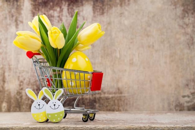 Frühlingsdekor, gelbe tulpen mit ostereiern.