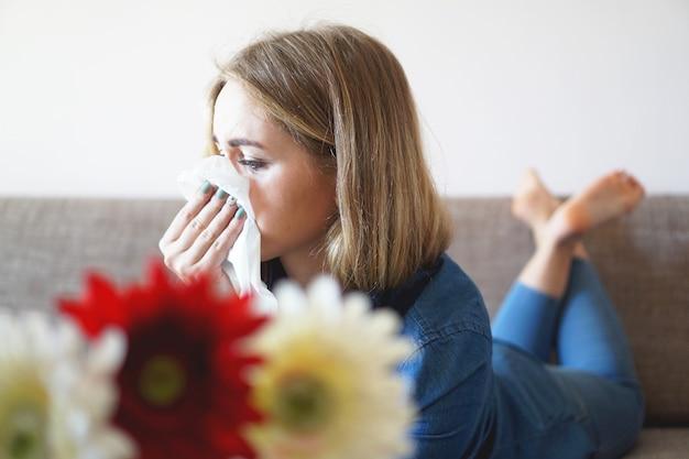 Frühlingserkältung oder allergien. ein junges attraktives mädchen ist allergisch gegen blumen, benutzt zu hause eine serviette