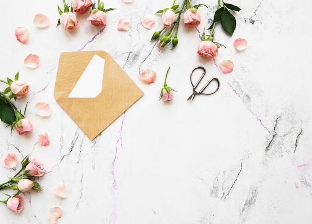 Frühlingsfeiertagsthema, -rosen und -brief auf einem weißen marmorhintergrund
