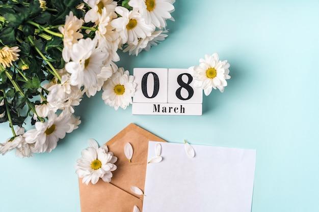 Frühlingsfeiertagszusammensetzung auf einem blauen hintergrund mit gänseblümchen und einem hölzernen kalender am 8. märz