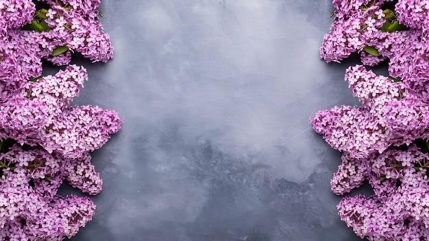 Frühlingsfliederblumen auf grauem hintergrund mit rahmen für text. banner