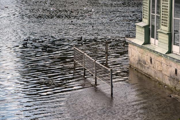 Frühlingsflut des wassers im fluss. hochwasser, haus mit wasser überflutet.