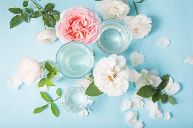 Frühlingsfrische weiße, rosa rosen verzerrt durch flüssiges wasser des glases auf blau.
