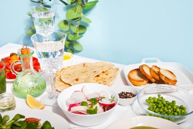 Frühlingsfrischer salat mit rettich und basilikum auf dem esstisch mit fladenbrot naan
