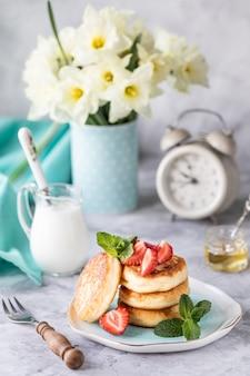 Frühlingsfrühstück mit blumen, käsekuchen und frischen beeren