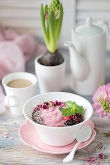Frühlingsfrühstück mit einer tasse kaffee auf einem hölzernen hintergrund. müsli mit erdbeeren, nüssen und milch.