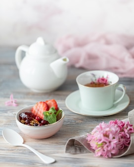 Frühlingsfrühstück mit granola und frischen erdbeeren und litschi und blumen auf hölzernem hintergrund.