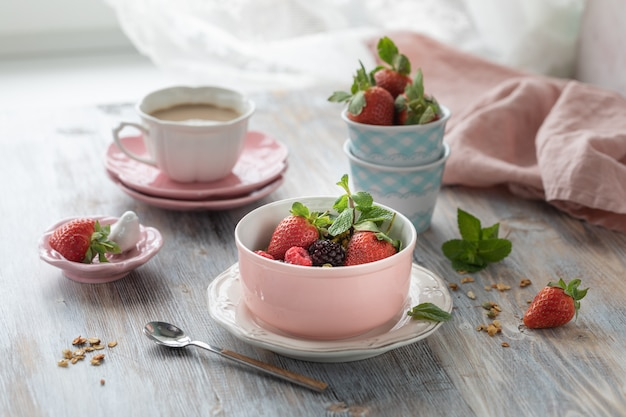 Frühlingsfrühstück mit müsli und frischen erdbeeren und litschi und blumen auf hölzernem hintergrund.