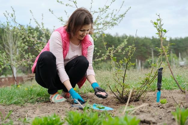 Frühlingsgartenarbeit, frau, die in handschuhen mit gartenwerkzeugen arbeitet, befruchtet