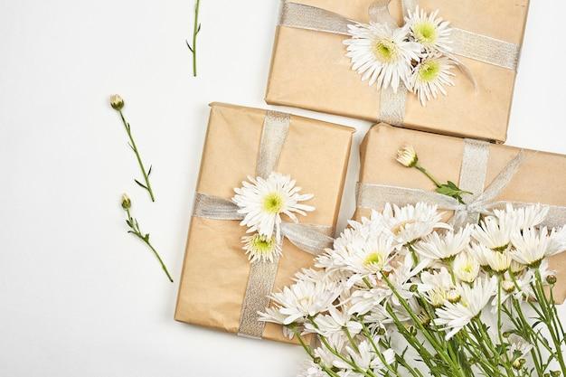 Frühlingsgeschenke. frische frühlingsblumen und geschenkboxen auf weißem hintergrund. machst du ein geschenk. empfangen eines