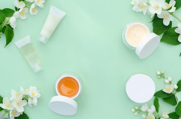 Frühlingsgesichtspflege. glascreme, kosmetisches produkt mit jasminblüten. natürliche pflanzliche bio-kosmetik. schönheitskonzept