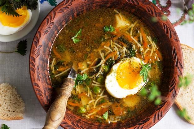 Frühlingsgrüne suppe mit kräutern, gemüse und erbsen, serviert mit ei und sauerrahm. rustikaler stil.