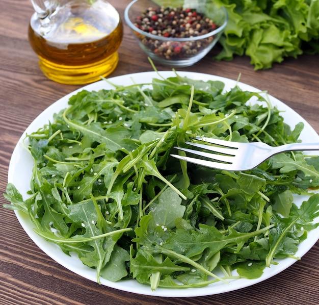 Frühlingsgrüner rucola-salat mit olivenöl