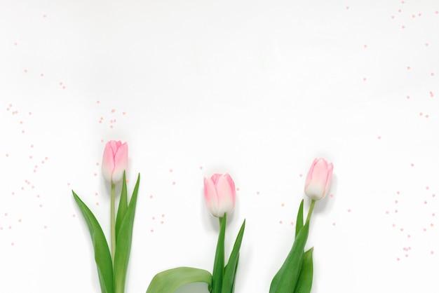 Frühlingsgrußkarte mit rosa tulpen und rosa konfetti auf weißem hintergrund und kopienraum. muttertag, valentinstag und internationaler frauentag am 8. märz