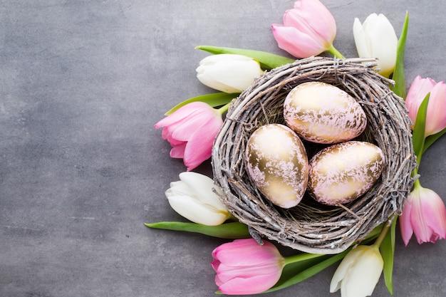 Frühlingsgrußkarte. ostereier im nest. frühlingsblumen tulpen.