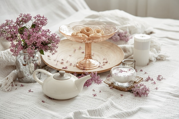 Frühlingsheim-stillleben mit lila blumen, süßigkeiten, milch und dekordetails.