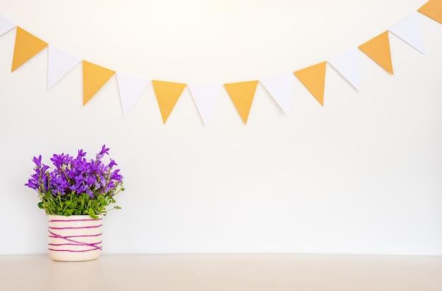 Frühlingshintergrund mit blumen und girlandenflaggen
