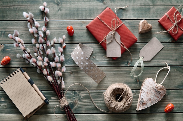Frühlingshintergrund mit bündel pussyweide, eingewickelten geschenken und frühlingsdekorationen