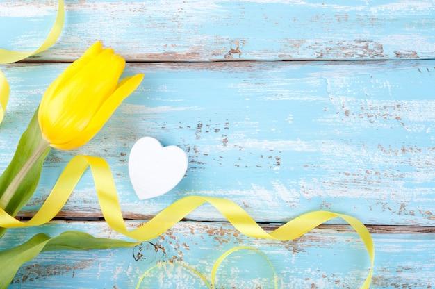 Frühlingshintergrund mit gelber tulpe mit band und herzen