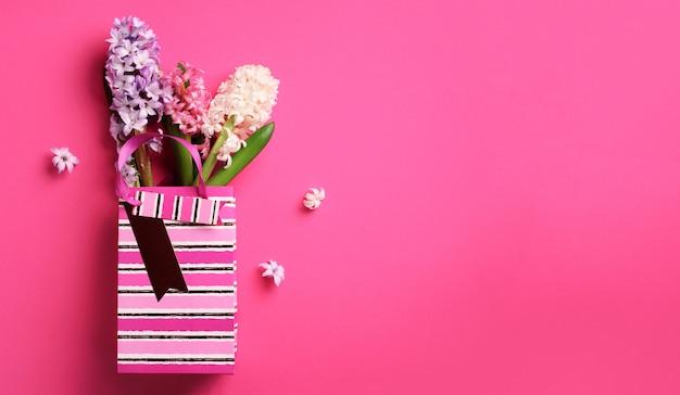 Frühlingshyazinthenblumen in der einkaufspapiertüte auf rosa schlagkräftigem pastellhintergrund.