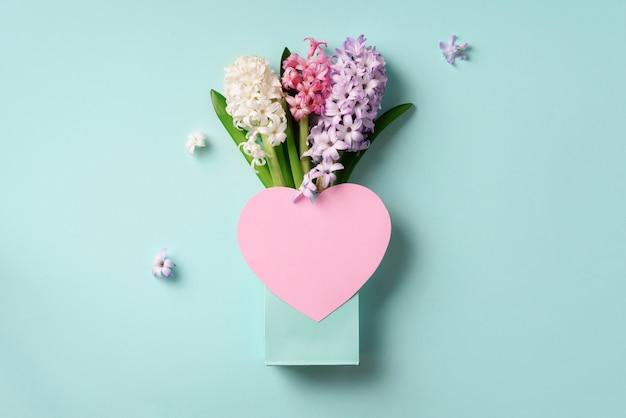 Frühlingshyazinthenblumen in der einkaufstasche, rosa papierherz.