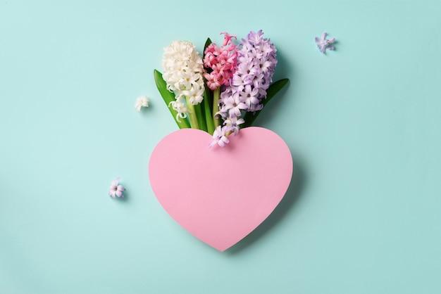 Frühlingshyazinthenblumen und rosa papierherz.