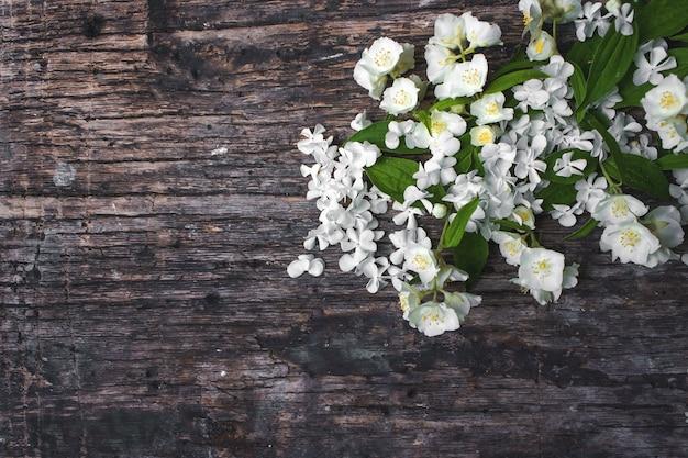 Frühlingsjasminblumen auf hölzernem hintergrund. valentinstag-grußkarte textfreiraum ansicht von oben.