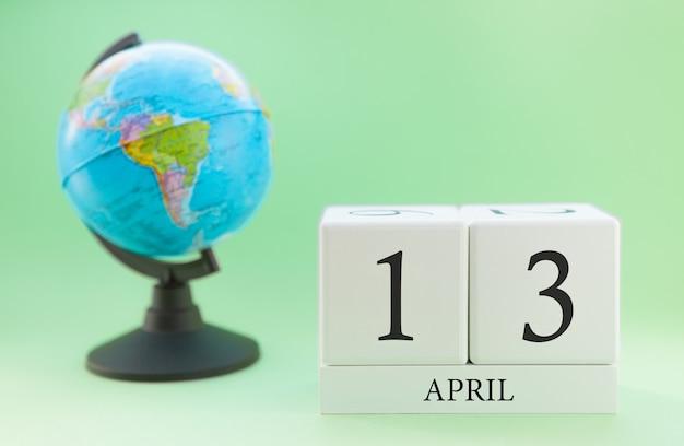 Frühlingskalender 13. april. teil eines sets auf unscharfem grünem hintergrund und kugel.