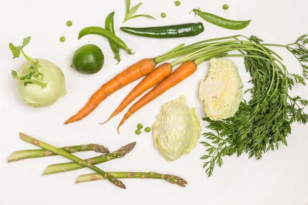 Frühlingskarotten mit grünen spitzen, grünen erbsen und wirsing. kohlrabi und limette auf dem tisch. weißer hintergrund. flach legen