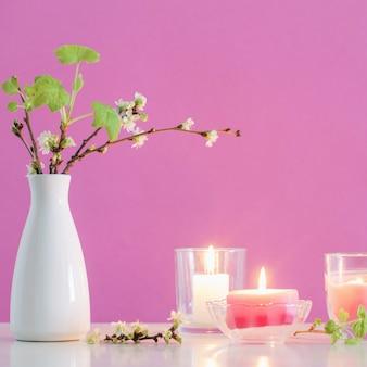 Frühlingskirschblumen und kerzen auf rosa hintergrund
