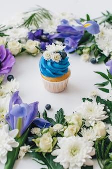 Frühlingskleiner kuchen auf einem weißen hintergrund mit blumen und früchten