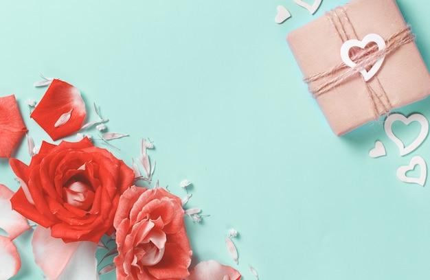 Frühlingskomposition mit rosen, blütenblättern, herzen und geschenkbox auf pastellhintergrund
