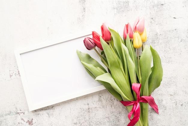 Frühlingskonzept. bunter tulpenstrauß und leerer rahmen auf weißem hintergrund mit kopienraum