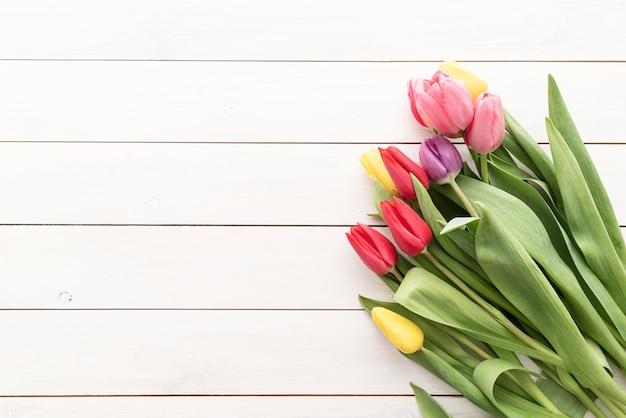 Frühlingskonzept. tulpenstrauß auf schwarzem hölzernem hintergrund mit kopienraum