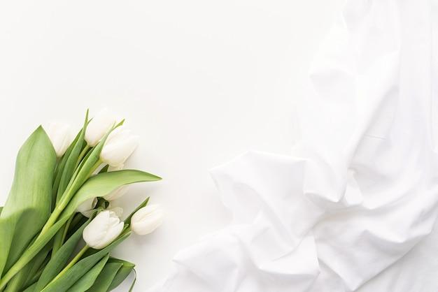 Frühlingskonzept. weißer tulpenstrauß und stoff für modellentwurf auf weißem hintergrund mit kopienraum
