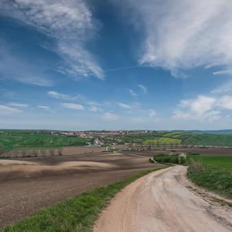 Frühlingslandschaft mit landwirtschaftlichen feldern, bäuerlichem hintergrund