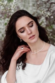 Frühlingslebensstil. modell, das nahe weißen blühenden bäumen ohne maskenlandschaft im freien aufwirft. träumendes mädchen mit lockigem haar.