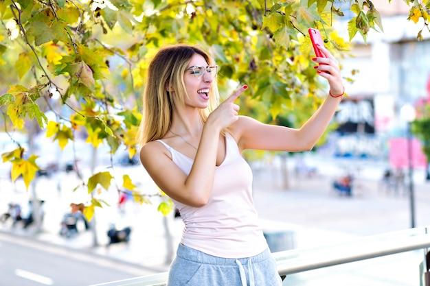 Frühlingslebensstilporträt der hübschen blonden frau, die selfie macht und auf video-chat mit ihrem freund, lässige sportliche kleidung, sonnige pastellfarben spricht.