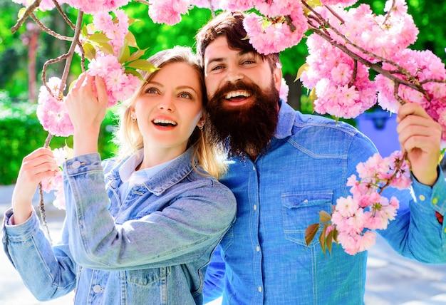 Frühlingsliebendes paar im blühenden garten. glückliche familie im sakura-blumenbaum.